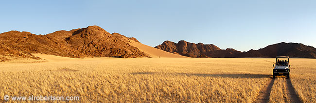 Evening, sundowner drive in a Landrover through the grass plains of the Namib Desert, Namibia