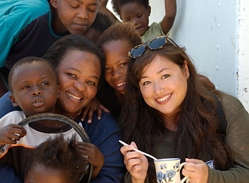 Nicci eating soup with Rosie and kids, Rosie's soup kitchen, Khyelitsha Township, South Africa