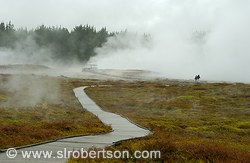 Steam vents, fumeroles and couple walking along boardwalk, Craters of the Moon Park