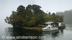 Deep sea fisherman's motel and fishing boat on small island at mouth of Doubtful Sound on the Tasman Sea