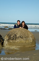 Man and woman posing behind the Moeraki Boulders, a spherical rock formations on East Coast, South Island beach