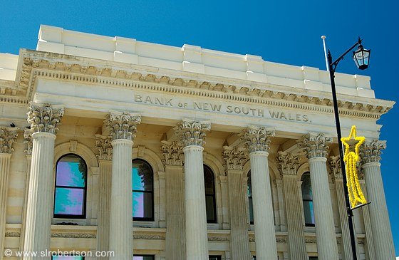 Limestone building with corinthian columns and Christmas decoration on lamp post - Bank of New South Wales, Oamaru