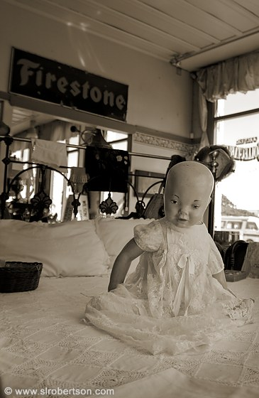 Antique porcelain baby doll sitting on iron bed in antique store, Oamaru