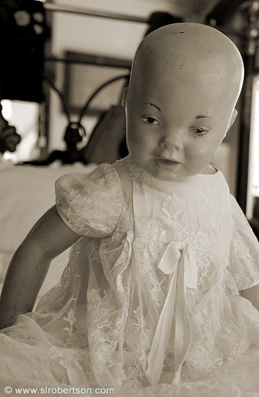 photo of antique porcelain baby doll sitting on iron bed in antique