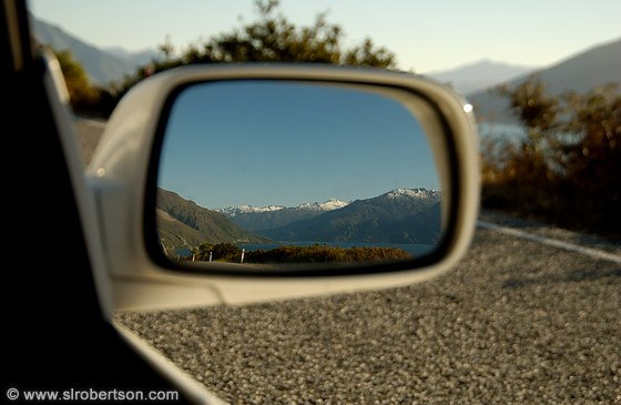View of Crown Range mountains in car side mirror