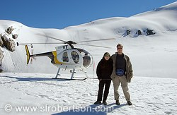 Couple on top of Fox Glacier with helicopter