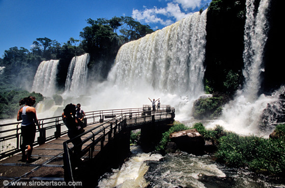 Tourists standing on wooden walkway below falls, Iguazu