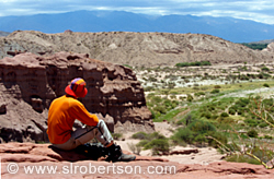 Bike rider takes a break on cliff overlooking Valles Calchaquies
