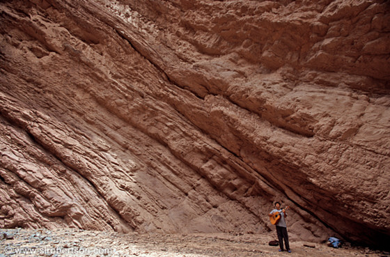 Guitar player singing in amphiteater-like box canyon, Calchaquies Valley, Salta