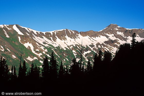 Snow covered mountain range and evergreen silhouettes near Paradise Divide, Crested Butte, Colorado